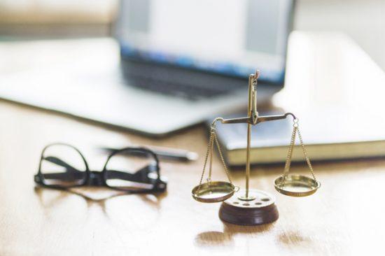 מאזניים זהב קטנות, משקפיים, וברקע מחשב נייד וספר