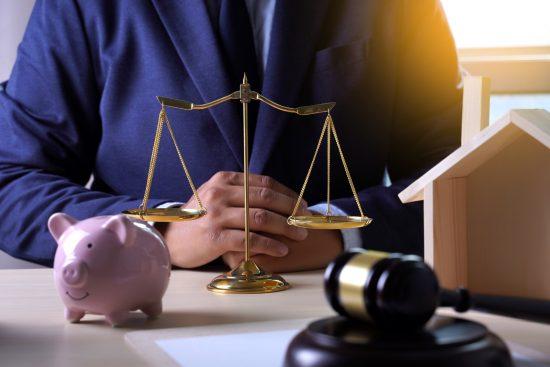 עורך דין בחליפה כחולה, יושב ליד שולחן שעליו מאזניים זהב, פטיש בית משפט וקופסת חיסכון חזיר