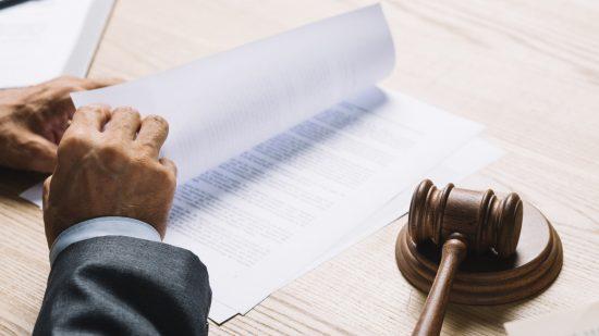 עורך דין מול שולחן עם מסמכים ופטיש בית משפט בצבע חום