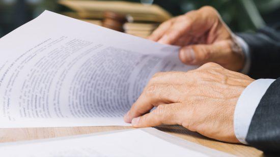 עורך דין עובר על מסמכים, וברקע ספר ופטיש בית משפט
